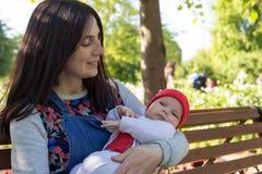 Junge Mutter hält ein neugeborenes Baby in ihren Armen für einen Weg im Park stockbild
