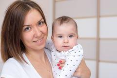 Junge Mutter hält ihr neugeborenes Baby stockfotos