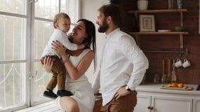 Junge Mutter hält ihren netten Sohn, der auf dem Fensterbrett zusammen mit jungem Vater sitzt Das Fenster wird mit verziert stock video