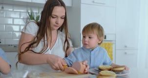 Junge Mutter hilft einem Kind, Burger in der Küche zu kochen stock footage