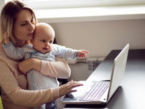 Junge Mutter im Innenministerium mit Computer und ihrem Baby Freiberufler oder Blogger, Arbeit und Kinderbetreuung Lizenzfreie Stockfotografie