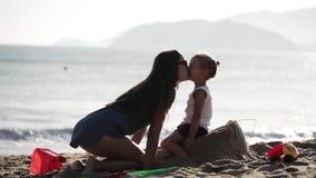 Junge Mutter im Kleid und kleine Tochter errichten Schloss mit Sand auf dem Strand stock footage