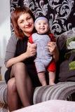 Junge Mutter ist frohe Holding ein kleines Kind in ihren Armen lizenzfreies stockbild