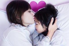 Junge Mutter küsst ihr Kind auf Bett stockfoto