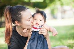 Junge Mutter küsst ihr nettes Baby auf der Backe Lizenzfreies Stockbild