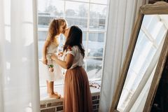 Junge Mutter küsst ihre kleine Tochterstellung auf dem Fensterbrett nahe bei dem Spiegel im vollen des hellen gemütlichen Raume stockfotos