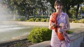 Junge Mutter mit Baby im Riemen lächelt, Smartphone halten stock footage