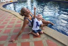 Junge Mutter mit Babytochtersitzen und -c$spielen Lizenzfreie Stockbilder