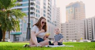 Junge Mutter mit dem Baby, das auf dem Gras im Park das Mittagessen essend sitzt stock video
