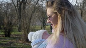 Junge Mutter mit dem Baby im Riemen Zeit im Park an der Freizeit verbringend stock footage