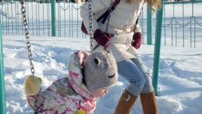 Junge Mutter mit dem Kind, das auf gesetztem im Freien des Schwingens im Winterpark schwingt Fallender Schnee, Schneefälle, Winte stock video footage