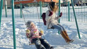Junge Mutter mit dem Kind, das auf gesetztem im Freien des Schwingens im Winterpark schwingt Fallender Schnee, Schneefälle, Winte
