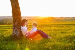 Junge Mutter mit dem kleinen Baby, das bei Sonnenuntergang sitzt Lizenzfreie Stockfotos