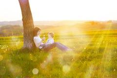 Junge Mutter mit dem kleinen Baby, das bei Sonnenuntergang sitzt Lizenzfreie Stockbilder