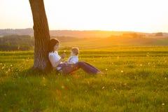 Junge Mutter mit dem kleinen Baby, das bei Sonnenuntergang sitzt Stockbilder
