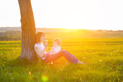 Junge Mutter mit dem kleinen Baby, das bei Sonnenuntergang sitzt Lizenzfreies Stockfoto