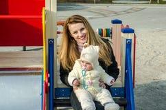 Junge Mutter mit dem langen Haar, das die Augen Ihres Babys auf dem Spielplatz untersucht Stockbild