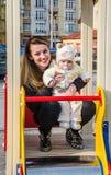 Junge Mutter mit dem langen Haar, das die Augen Ihres Babys auf dem Spielplatz untersucht Stockfotografie