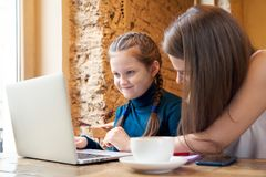Junge Mutter mit dem langen Haar, das an einem Tisch in einem Café mit ihm sitzt stockfoto