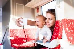 Junge Mutter mit dem Smartphone, der mit Baby mit dem Zug reist Stockbilder