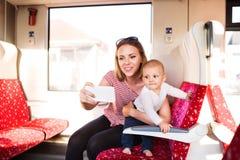 Junge Mutter mit dem Smartphone, der mit Baby mit dem Zug reist Lizenzfreies Stockfoto