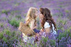 Junge Mutter mit der jungen Tochter, die auf dem Feld des Lavendels lächelt Tochter, die auf Mutterhänden sitzt Mädchen in buntem lizenzfreies stockbild
