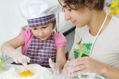 Junge Mutter mit der kleinen Tochter, die Plätzchen zubereitet lizenzfreies stockbild