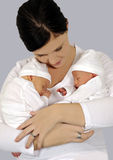 Junge Mutter mit Doppelbabys in der weißen Kleidung Stockbild