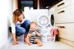 Junge Mutter mit einem Baby, das Hausarbeit tut stockbild