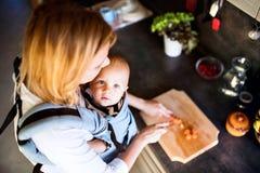 Junge Mutter mit einem Baby, das Hausarbeit tut lizenzfreies stockfoto