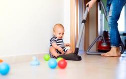 Junge Mutter mit einem Baby, das Hausarbeit tut stockfotografie