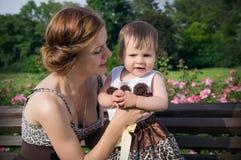 Junge Mutter mit einem Kind auf der Natur sitzt auf einer Bank Lizenzfreies Stockfoto