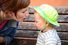 Junge Mutter mit einem Kleinkind, das auf einer Holzbank sitzt Lizenzfreie Stockfotos