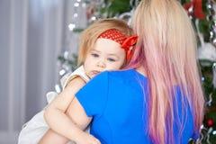 Junge Mutter mit einem müden Baby vor Weihnachtsbaum Weihnachtsfamilien-Porträt lizenzfreies stockfoto