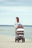 Junge Mutter mit einem Spaziergänger Stockfotos