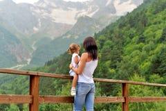 Junge Mutter mit einer kleinen Tochter, die in der Natur in den Bergen stillsteht stockfotos