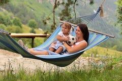 Junge Mutter mit einer kleinen Tochter, die in der Natur in den Bergen stillsteht stockbild