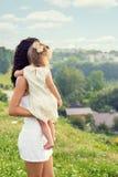 Junge Mutter mit einer kleinen Tochter in seinen Händen, die am Rand der Klippe und der Blicke in den Abstand über der Stadt steh Lizenzfreies Stockfoto