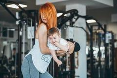 Junge Mutter mit ihrem jungen Sohn in der Turnhalle lizenzfreie stockbilder