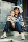 Junge Mutter mit ihrem Kind vor den Toren eines Tempels lizenzfreies stockfoto