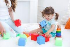 Junge Mutter mit ihrem Kinderspiel zusammen Lizenzfreie Stockbilder