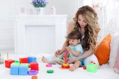 Junge Mutter mit ihrem Kinderspiel zusammen Lizenzfreies Stockbild