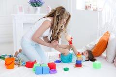 Junge Mutter mit ihrem Kinderspiel zusammen Stockfotos