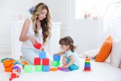 Junge Mutter mit ihrem Kinderspiel zusammen Stockbild