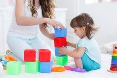 Junge Mutter mit ihrem Kinderspiel zusammen Lizenzfreies Stockfoto
