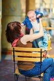 Junge Mutter mit ihrem kleinen Sohn in einem Straßencafé Lizenzfreies Stockfoto