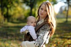 Junge Mutter mit ihrem Schätzchen in einem Träger Lizenzfreie Stockbilder