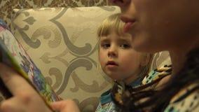 Junge Mutter mit ihrer kleinen Tochter, die zusammen das Buch liest 4K UltraHD, UHD stock video footage