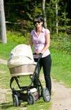 Junge Mutter mit Pram Lizenzfreie Stockfotografie