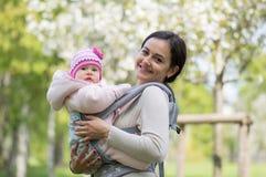 Junge Mutter mit Säuglingsbaby im Riemen lizenzfreie stockbilder